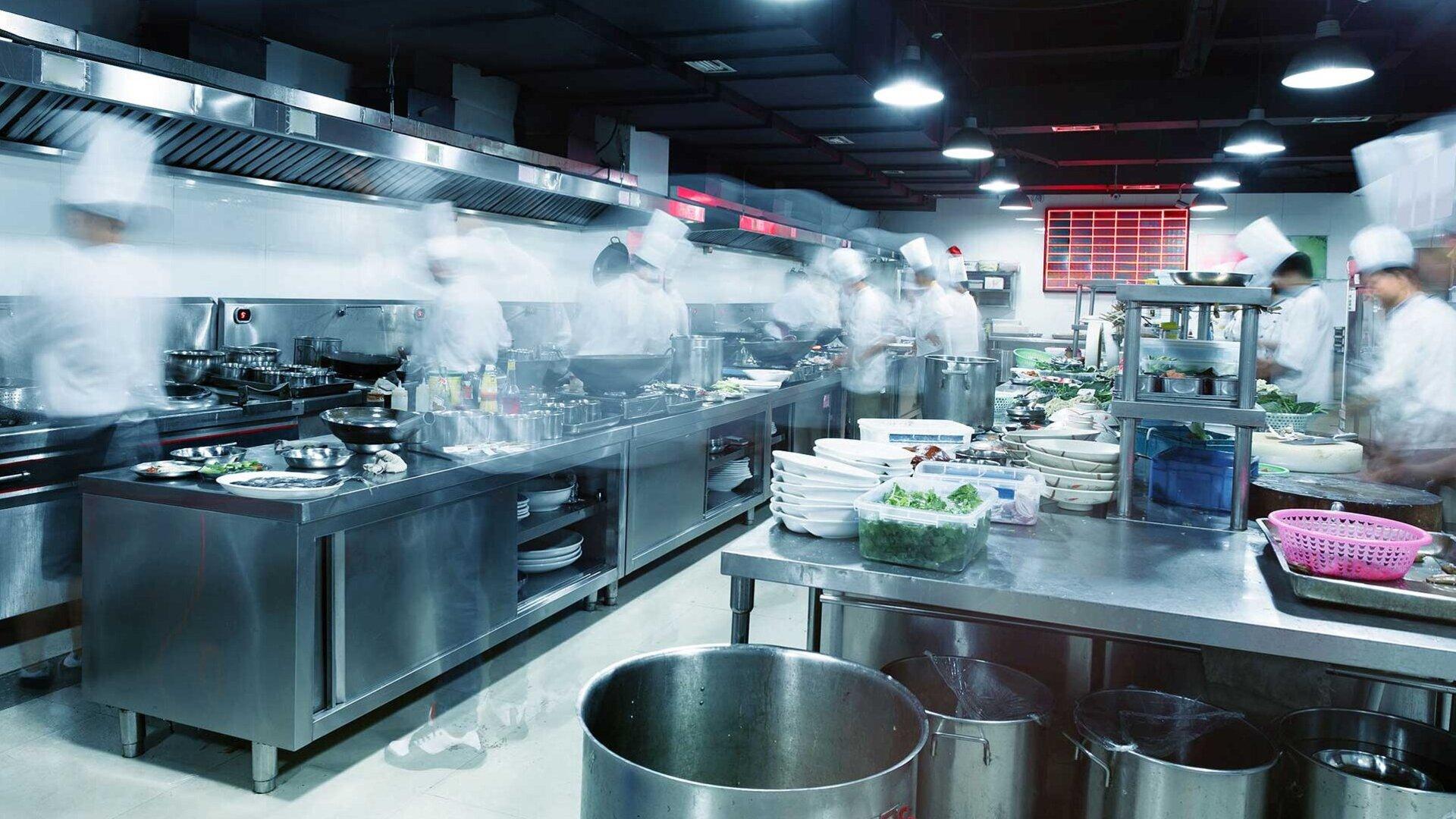 Zahlreiche Köche arbeiten in einer großen Gastroküche