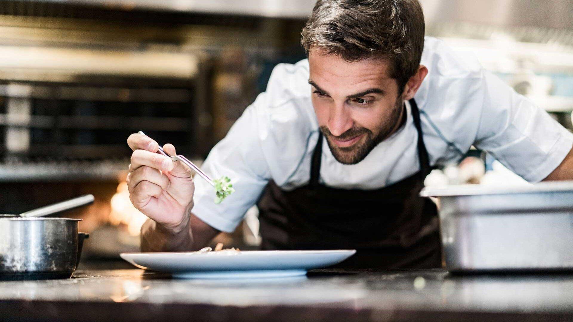 Cook is preparing food on plate