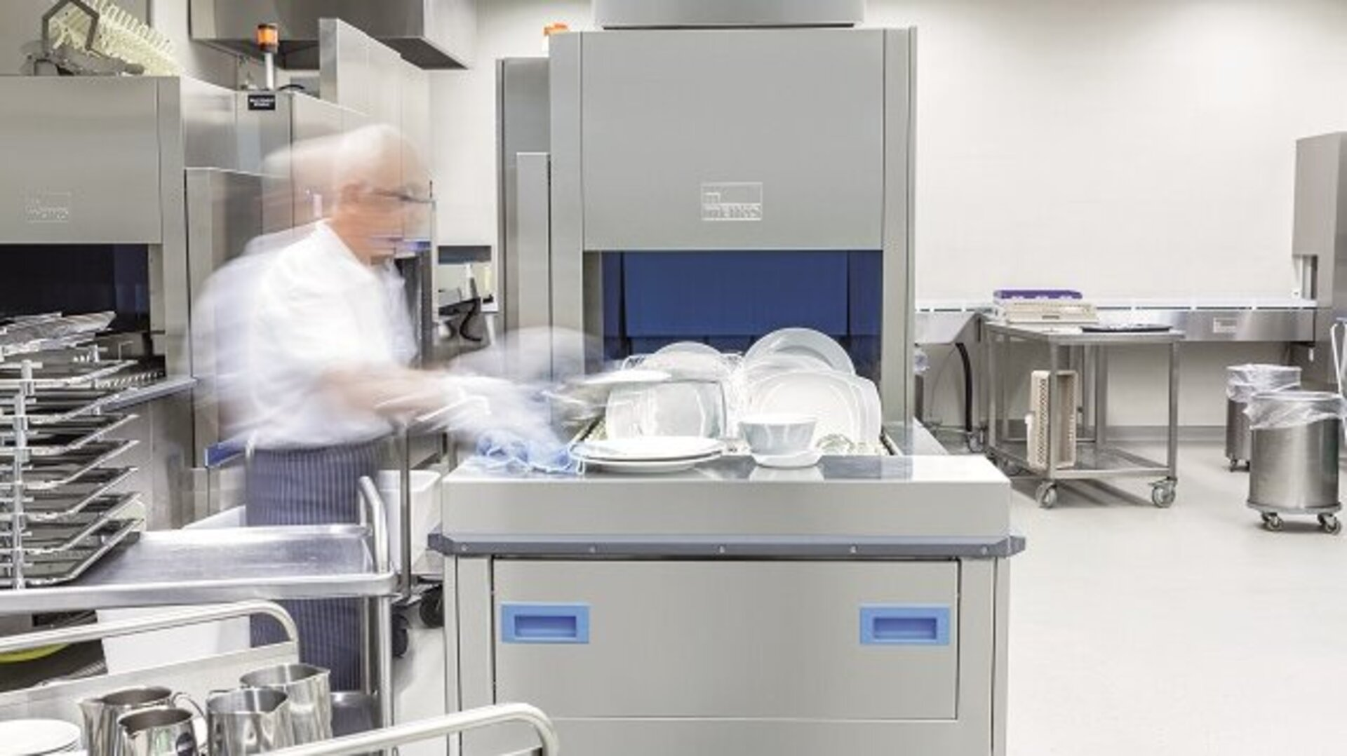 An employee uses a MEIKO industrial dishwasher in a back-of-house kitchen environment