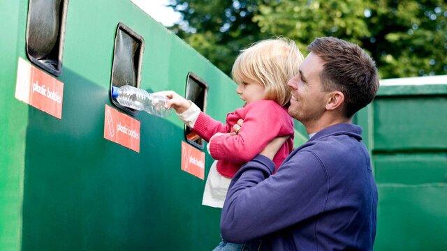 Mann und Kind recyceln eine Flasche