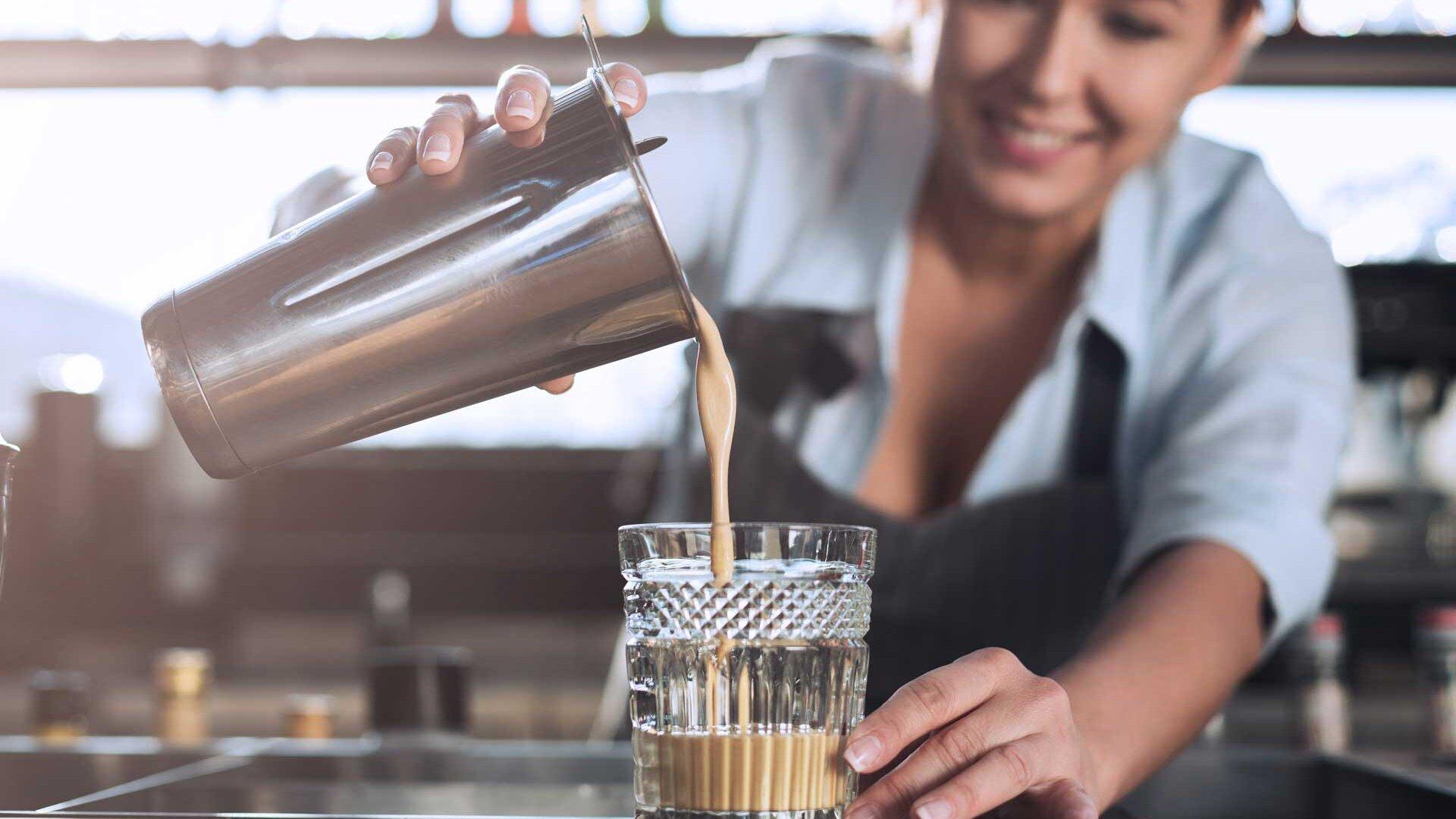 Bartenderin gießt Cold Brew Cocktail in Glas